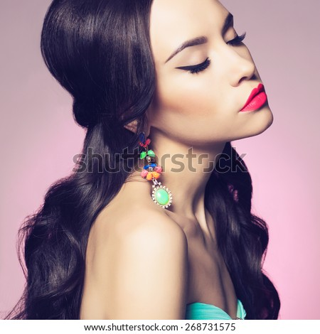 Fashion studio portrait of beautiful young woman with earring. Jewelry and accessories  - stock photo