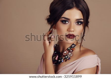 fashion studio portrait of beautiful young woman with elegant hairstyle and luxurious necklace - stock photo