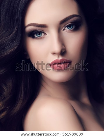 fashion studio portrait of beautiful young woman with long dark hair and blue eyes with bright makeup - stock photo