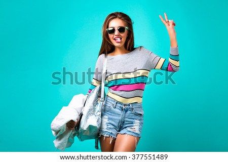 Fashion studio portrait of glamour sportive girl, smart casual outfit, cute emotions, stylish hipster clothes sunglasses and backpack, spring pastel colors. mini hipster denim shorts crazy emotions. - stock photo