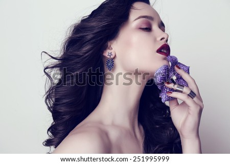 fashion studio portrait of gorgeous woman with dark hair and bright makeup with manicured nails and bijou - stock photo