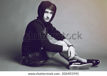 Fashion studio portrait of handsome guy wearing black hoody, black and white colors. - stock photo