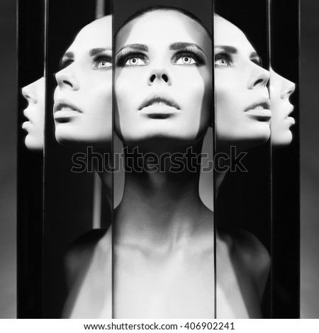 Fashion studio portrait of woman and mirrors on black background - stock photo