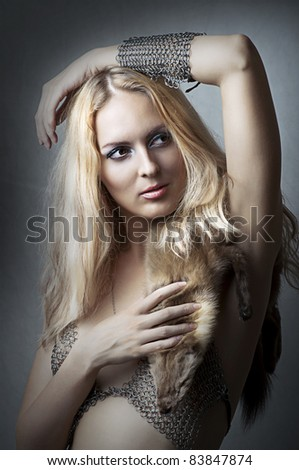 Fashion studio portrait of young adult beautiful sexy model in chain armour bikini