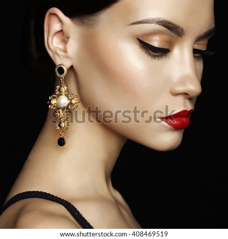 Fashion studio portrait of young beautiful lady with earring on black background - stock photo
