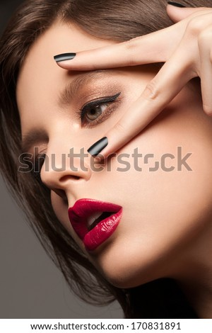 Fashion studio portrait of young beautiful woman with bright makeup and black manicure - stock photo