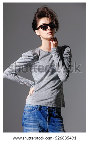 Fashion studio portrait of young woman in jeans with sunglasses posing