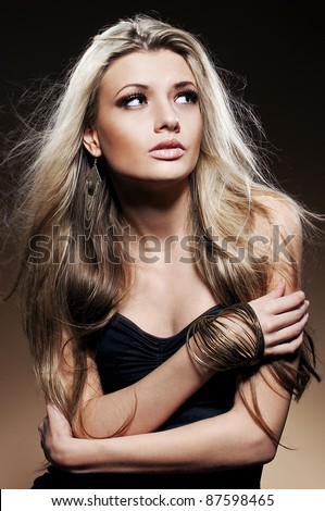 Fashion studio portrait of young woman with long blond hair