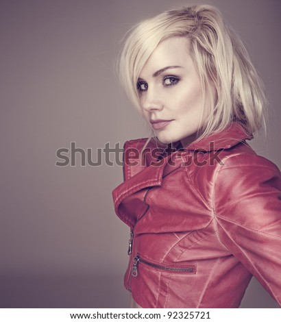 Fashion studio shot of attractive young blonde woman in stylish leather jacket - stock photo