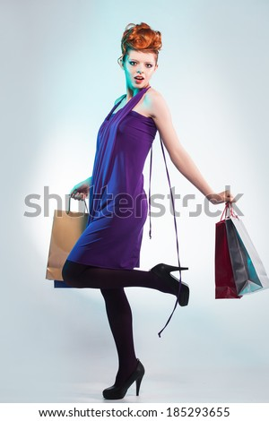 Fashion studio shot of beautiful woman with shopping bag. Professional makeup and hairstyle