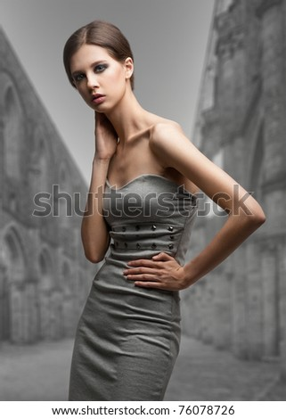 Fashion studio shot of young beautiful woman wearing grey dress with bright makeup and hairstyle - stock photo