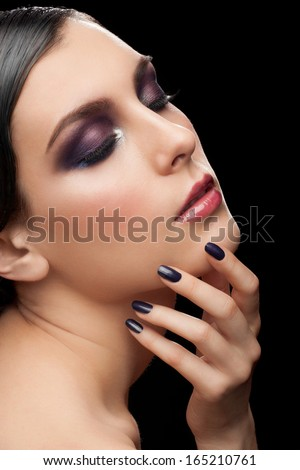 Fashion studio shot of young beautiful woman with bright violet makeup and manicure