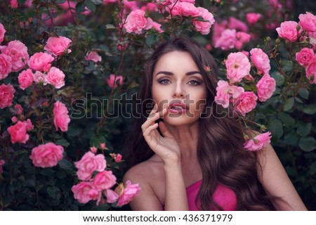 Fashion style beauty romantic portrait of young pretty beautiful woman with long curly hair posing between pink roses. Stunning girl looking at you or in camera - stock photo