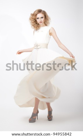 Fashion style - luxurious young woman in light flying dress posing in studio. Series of photos