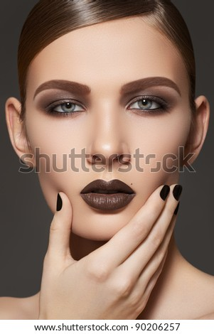 Fashion style, manicure, cosmetics and make-up. Dark lips makeup & nails polish. Close-up portrait of female model with brown lipstick, black fingernails and clean skin. Shiny slicked back hairstyle - stock photo