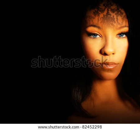 Fashion style portrait of a beautiful female model with exotic makeup and dark background with lots of copy space - stock photo