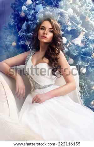 Fashion style portrait of elegant pretty girl in christmas interior. Young beautiful woman in white dress sitting at sofa against festive christmas tree. - stock photo