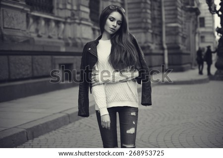 Fashion style portrait of young beautiful calm female model posing at city street with magnificent architecture. Monochrome portrait.