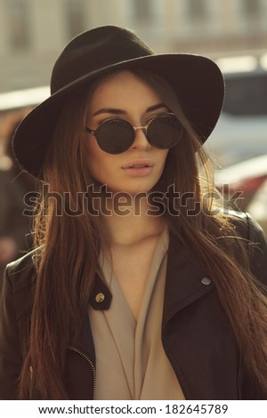 fashion style portrait of young trendy girl in fashionable hat and sunglasses - stock photo