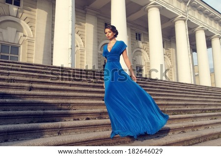 Fashion style portrait. Young elegant woman in blue long flying dress posing at stairway against old city building  - stock photo