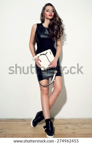 Fashion style studio portrait of young stunning woman in black sexy minidress with white handbag. Beautiful girl with long curly hair and red lips.