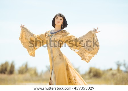 Fashion stylish beauty woman with black short haircut and professional make-up of Cleopatra. Girl standing in golden dress outdoors in desert. Hot sunny weather - stock photo