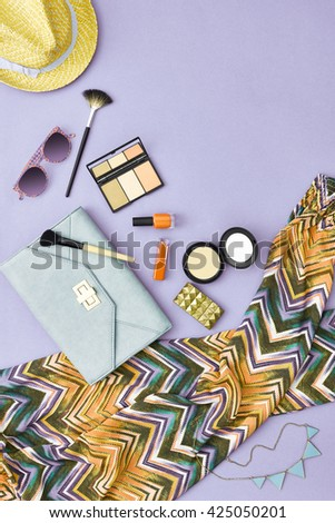 Fashion stylish clothes, cosmetics, makeup accessories set. Urban summer girl colorful outfit. Stylish handbag clutch, trendy pants, necklace, sunglasses. Woman essentials. Unusual overhead, top view - stock photo