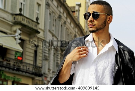 Fashion stylish young african man in sunglasses and black rock leather jacket. - stock photo