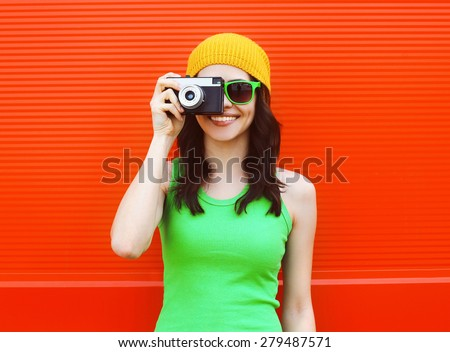 Fashion, summer and people concept - pretty cool girl in sunglasses with retro camera having fun against colorful red wall - stock photo
