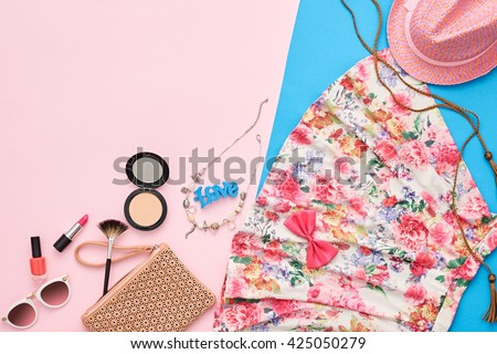 Fashion summer girl clothes accessories set. Woman essentials. Cosmetics, makeup. Stylish beige handbag clutch, trendy dress, hat, necklace, sunglasses . Unusual overhead outfit, top view on pink - stock photo