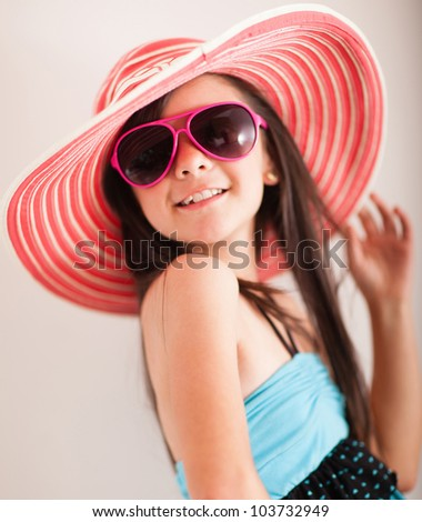 Fashion summer girl wearing a hat and posing for the camera - stock photo