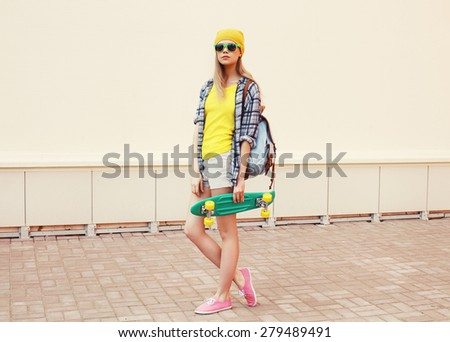 Fashion summer hipster cool woman in sunglasses and colorful clothes with skateboard outdoors  - stock photo