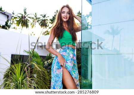 Fashion summer portrait of amazing seductive beautiful woman with bright make up and long hairs, wearing stylish crop top and bright printed chiffon skirt, posing on vacation in tropical country. - stock photo