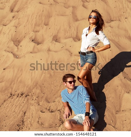 Fashion summer stylish couple posing outdoor on the beach and having fun together. - stock photo