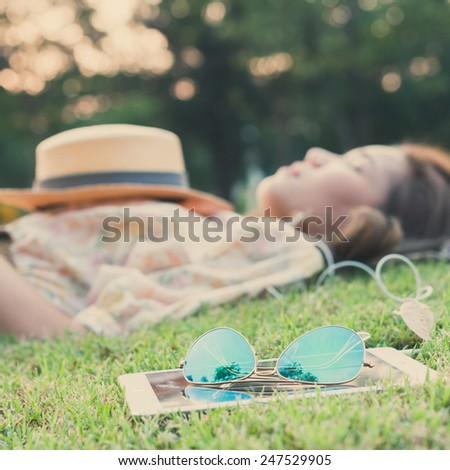 fashion sun glasses with young woman sleeping in background, vintage style - stock photo