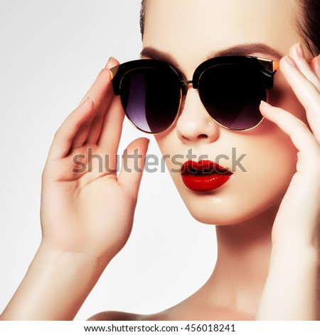 Fashion sunglasses. Sexy woman in swimsuit with golden sunglasses and fashion makeup. Glamour shot of a beautiful model with red lips. Young girl posing in white swimsuit a on white background