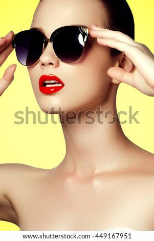 Fashion sunglasses. Sexy woman in swimsuit with golden sunglasses. Glamour shot of a beautiful model in white bikini and dark sunglasses. Young girl posing in white swimsuit a on yellow background - stock photo