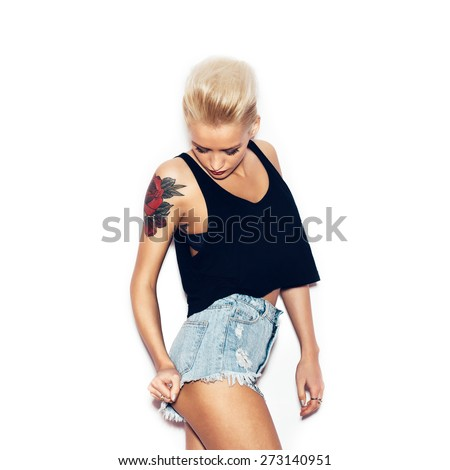 Fashion swag girl with tattoo in black t-shirt and jeans shorts.  White background, not isolated - stock photo