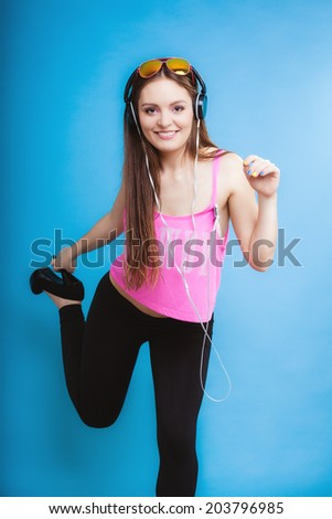 Fashion teen girl headphones listen music mp3 player, Fresh energetic young woman relax happy and dancing blue background
