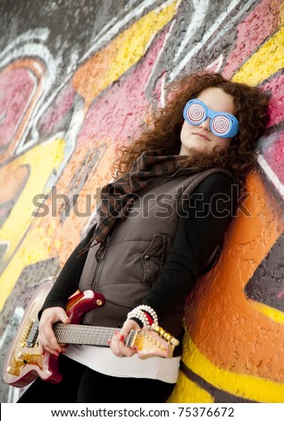Fashion teen girl with guitar at graffiti background. - stock photo