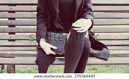 Fashion teen holding black clutch sitting on park bench in spring time. Instagram style - stock photo