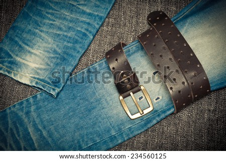 Fashion trend: blue shabby jeans and a leather belt with a buckle - stock photo