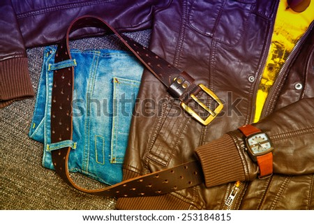 Fashion trend: leather jacket, blue jeans, a belt with a gold buckle, watch. Photo toned in yellow and purple - stock photo
