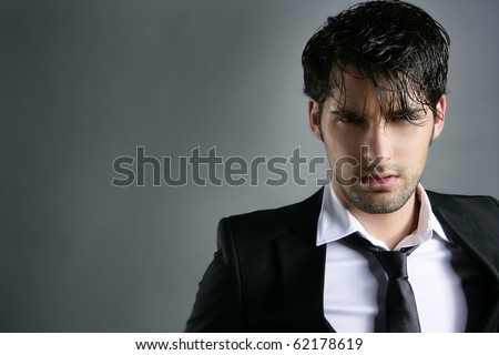Fashion trendy suit young handsome man messy hairstyle dark portrait on gray