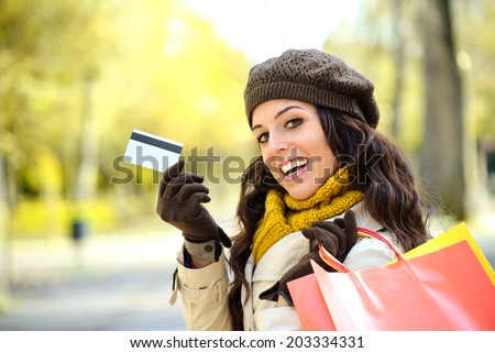 Fashion trendy woman showing credit card and carrying shopping bags after buying on autumn. Caucasian brunette shopper spending money. - stock photo