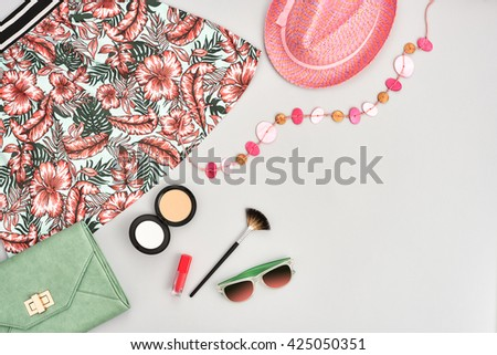 Fashion urban summer outfit, girl clothes set, cosmetics, makeup accessories. Stylish handbag clutch, trendy pink dress, necklace hat, sunglasses. Woman essentials. Unusual overhead, top view on gray - stock photo