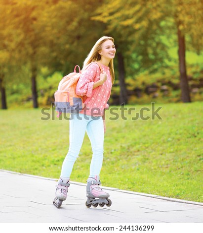 Fashion, vacation and people concept - pretty stylish smiling girl rollerblading in the city park in sunny day - stock photo