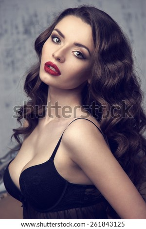 Fashion vogue style beauty portrait of young pretty beautiful brunette woman. Stunning caucasian female model with curly or wavy dark hair and red lips looking at you. Gray wall background
