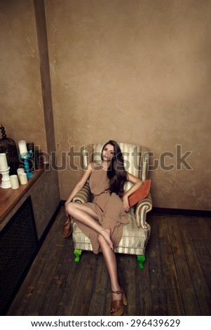 Fashion vogue style portrait of young beautiful female model sitting in a chair in brown wooden interior - stock photo