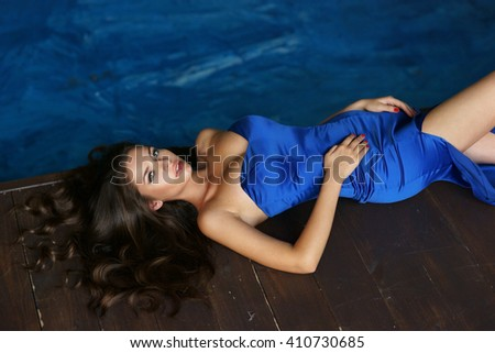 Fashion vogue style portrait of young beautiful stylish lady lying on wooden floor. Sexy pretty woman in elegant evening blue dress - stock photo
